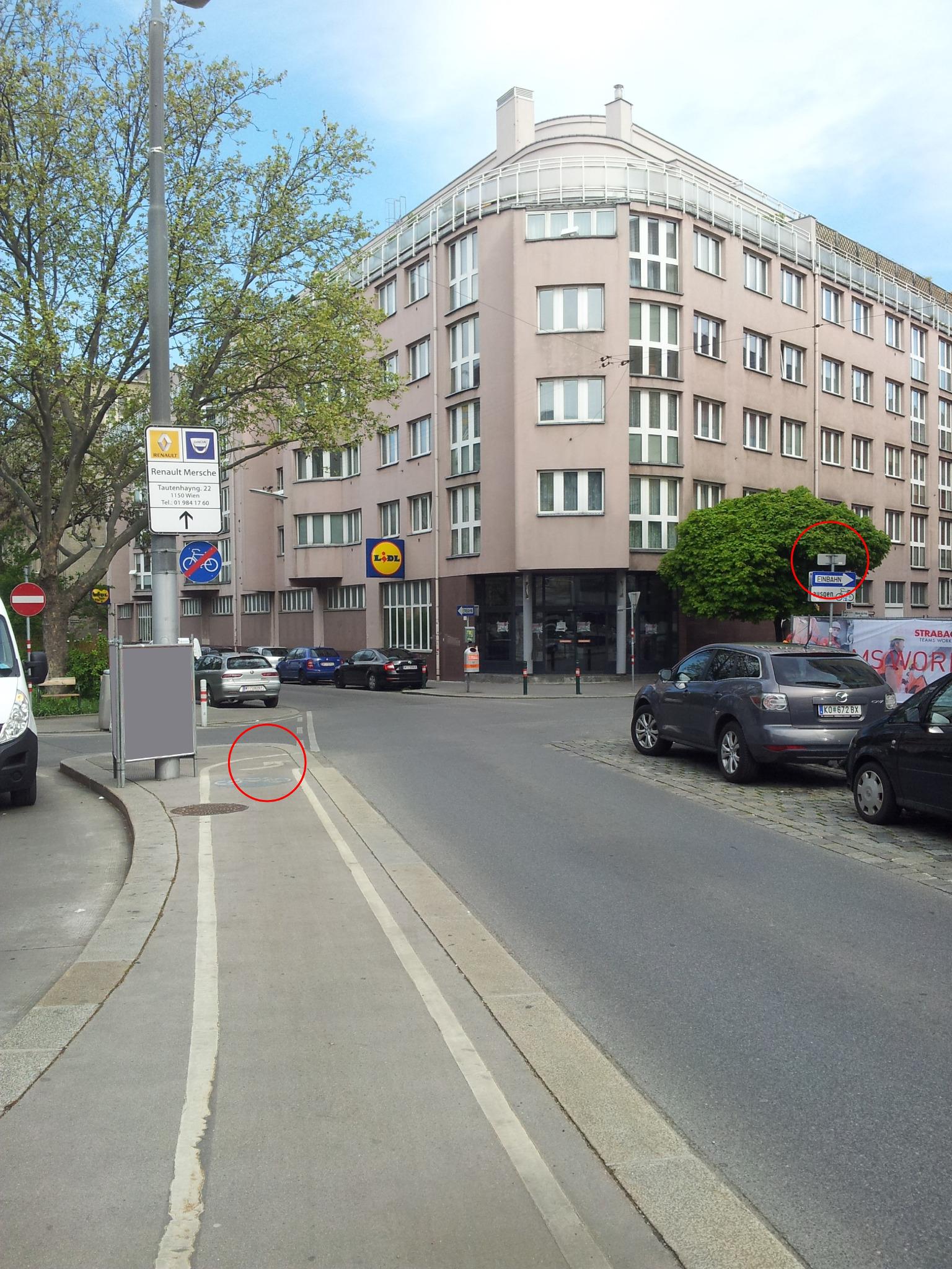Abb. 3: Foto vom Einrichtungsradweg in Richtung der Radroute. Der rote Kreis links markiert den Linksabbiegen-Pfeil auf die Schanzstraße (siehe Punkt 3). Der rote Kreis rechts markiert den Wegweiser Richtung Schmelz - der nur von der anderen Seite zu lesen ist (siehe Punkt 4). Die Sperrlinie (siehe Punkt 1) ist hier auch sichtbar, oberhalb vom linken roten Kreis.